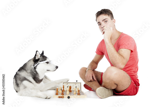 man is playing chess with a dog