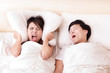 Young woman disturbed by the snores of her husband