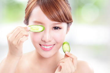 beautiful woman holding cucumber slices on face