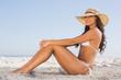 Attractive brunette in white bikini posing while sitting