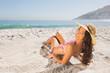 Smiling attractive young woman in pink bikini sunbathing