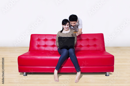 Asian couple pay online using credit card at home