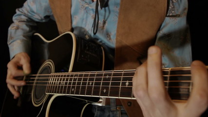 male hands play on acoustic guitar