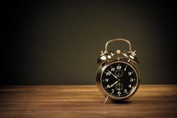 Retro alarm clock on table on dark background