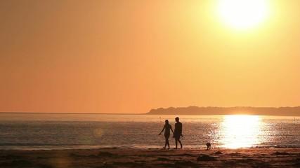 Couples se promène en bord de plage sous le soleil couchant