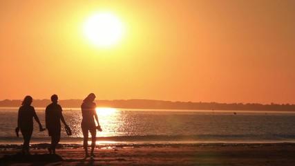 femme se promène sur la plage sous le soleil couchant