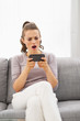 Concerned young woman sitting on sofa and reading sms