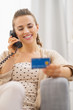 Happy woman with credit card talking phone while sitting on sofa