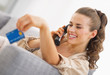 Happy young woman playing with credit card while talking phone