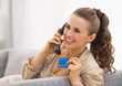 Happy young woman with credit card talking phone