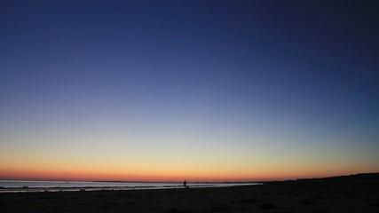 homme marche à la tomber de la nuit sur la plage