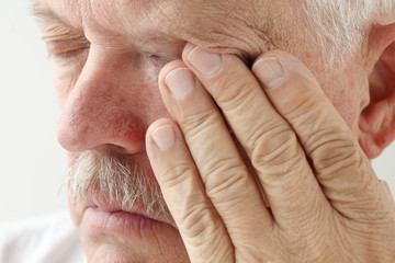 senior man has eyestrain and fatigue