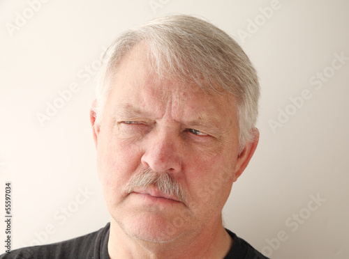older man has a distrusting look