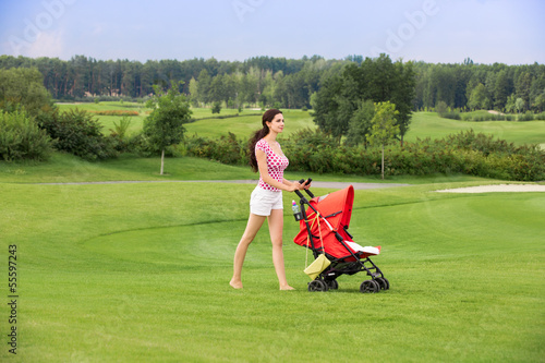 Happy young mother with baby in buggy walking