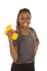 woman in gray shirt fitness yellow weights curl one hand