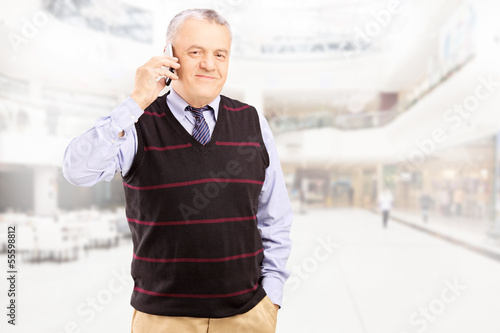 Smiling gentleman talking on a phone and posing in shopping mall