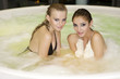 Two young beautiful girls in tub