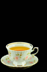porcelain tea cup full of tea and green teapot on a black backgr