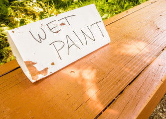 Hand made wet paint sign on a wooden park bench