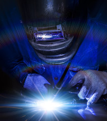 Worker welding the steel part