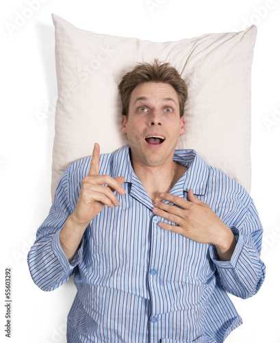 Man in bed in pajamas on pillow with idea