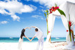 loving couple on wedding day on tropical beach near bamboo arch