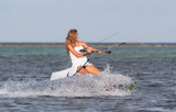 young beautiful woman in wedding dress kitesurfing on water back
