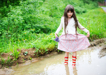 Elegant child girl standing in a puddle