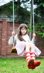 Elegant child girl swinging in the park