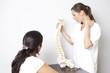 ärztin zeigt Patientin Modell einer Wirbelsäule