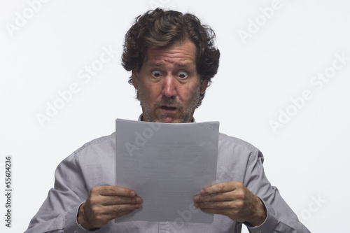 Business man reading report looking shocked, horizontal