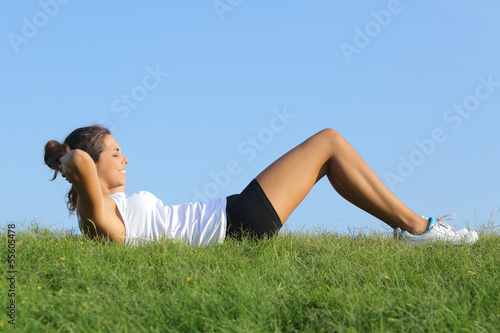 Beautiful woman doing crunches with the sky in the background