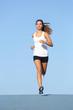 Front view of a beautiful sportswoman running towards camera