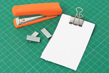 Blank note and stapler on Cutting mat.