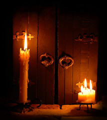 Two candlesticks with candles on the closed door background