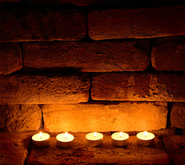 Five tea candles on brick wall background