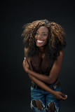 Joyful laughing African American woman against a dark background