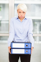Tired woman with heavy binders in her hands