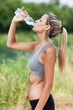 Young woman is drinking water after running session