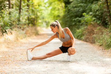 Sexy blonde woman is doing stretching exercises
