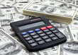 calculating income: calculator near a pile of dollars