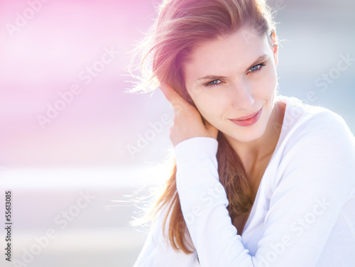 Delightful young woman touches her hair