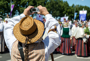Man in latvian national costume take a photo