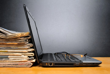 Laptop mit Zeitungen