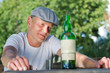 Depressed man looking at a bottle of white wine