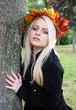 Junge Frau umarmt Baum im Herbst
