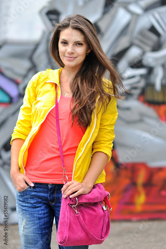 Young woman in bright clothes posing outdoors