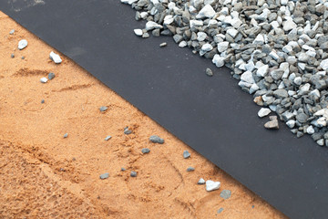 Geotextile layer between gray gravel and sandy ground