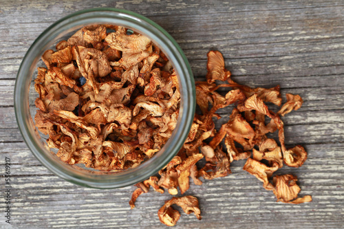 Dried Chanterelle mushrooms in jar on wooden table