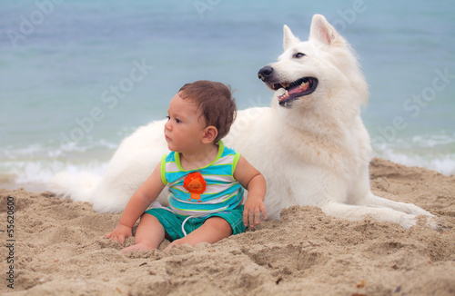 A sweet baby and his swiss white shepherd dog